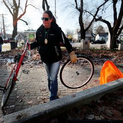 Jamie Pluta, an environmental health specialist, picks up a bike that had been left in Taufer Park in Salt Lake City as health department officials, Utah Highway Patrol troopers and Salt Lake City police officers clean up a homeless camp on Tuesday, Dec. 10, 2019.