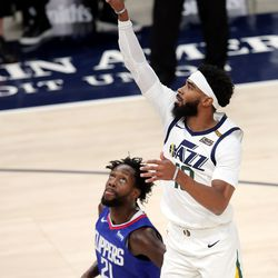 Utah Jazz guard Mike Conley (10) pushes up a shot over LA Clippers guard Patrick Beverley (21) as the Utah Jazz and LA Clippers play in an NBA basketball game at Vivint Smart Home Arena in Salt Lake City on Friday, Jan. 1, 2021.