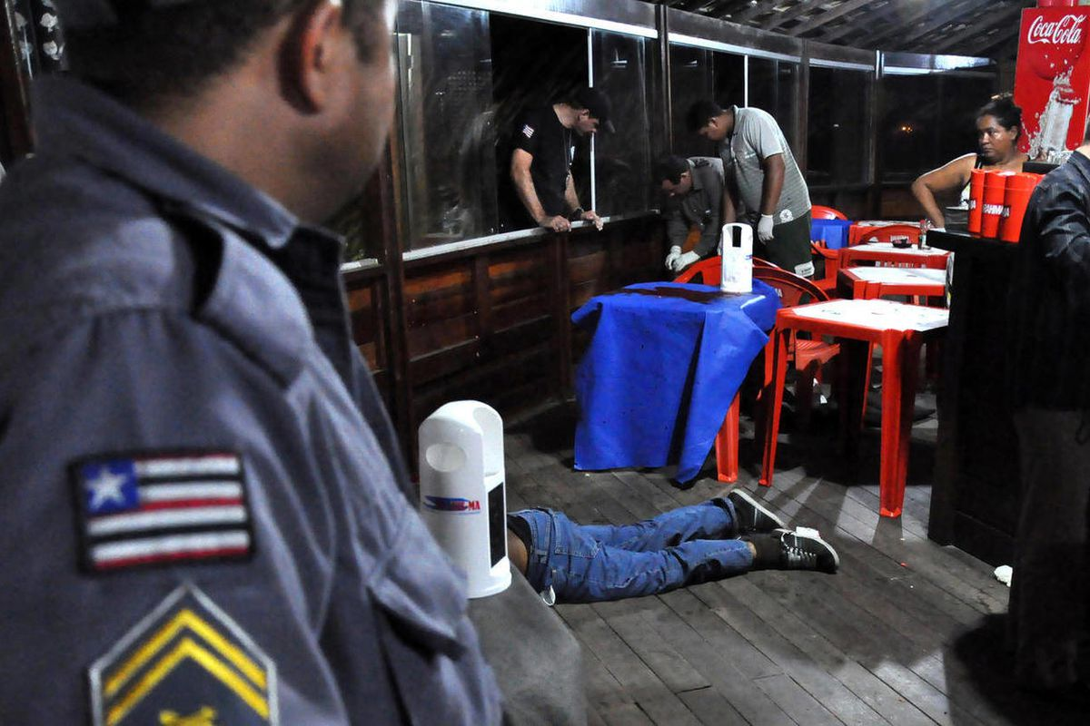 The body of Brazilian journalist Decio Sa, center, lies on the ground after being shot at a restaurant and bar in Sao Luis, Maranhao state, Brazil, Monday, April 23, 2012.  Sa, a political reporter for the O Estado do Maranhao newspaper in northeastern Br