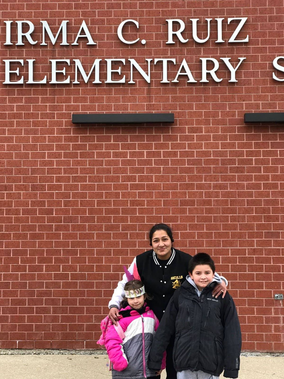 Tania Ibarra (center) and her two grandchildren, Sandra and Frank, outside of Irma C. Ruiz Elementary.