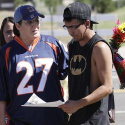 """Shelly Fradkin, left, and Isaac Pacheo, right, cry as they look at photos of their friend Alex Sullivan, Saturday, July 21, 2012, as they visit a memorial near the movie theater in Aurora, Colo.  Twelve people were killed and dozens were injured in the attack early Friday at the packed theater during a showing of the Batman movie, """"The Dark Knight Rises.""""   Police have identified the suspected shooter as James Holmes, 24. (AP Photo/Ted S. Warren)"""