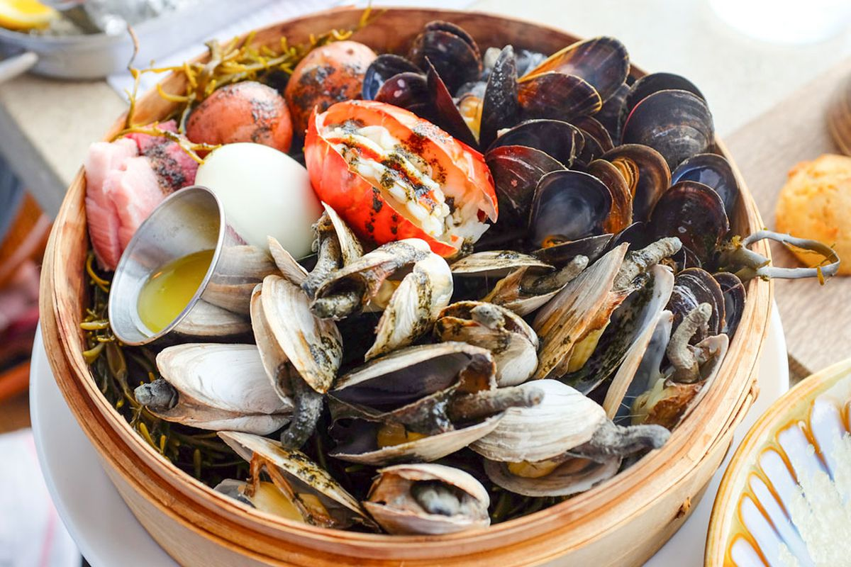 Steamer basket full of clams, mussels, potatoes, and other clambake ingredients
