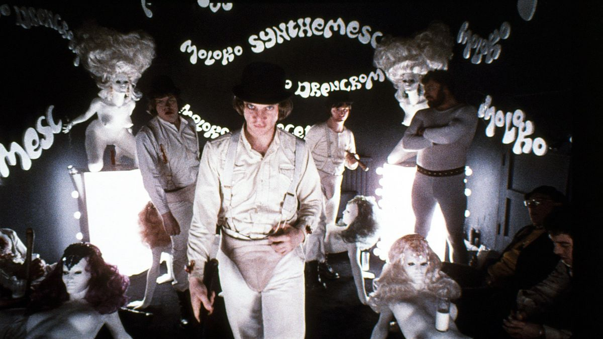 Malcolm McDowell as Alex in A Clockwork Orange stands in a darkened milk bar full of naked female mannequins, with fictional drug names all over the walls