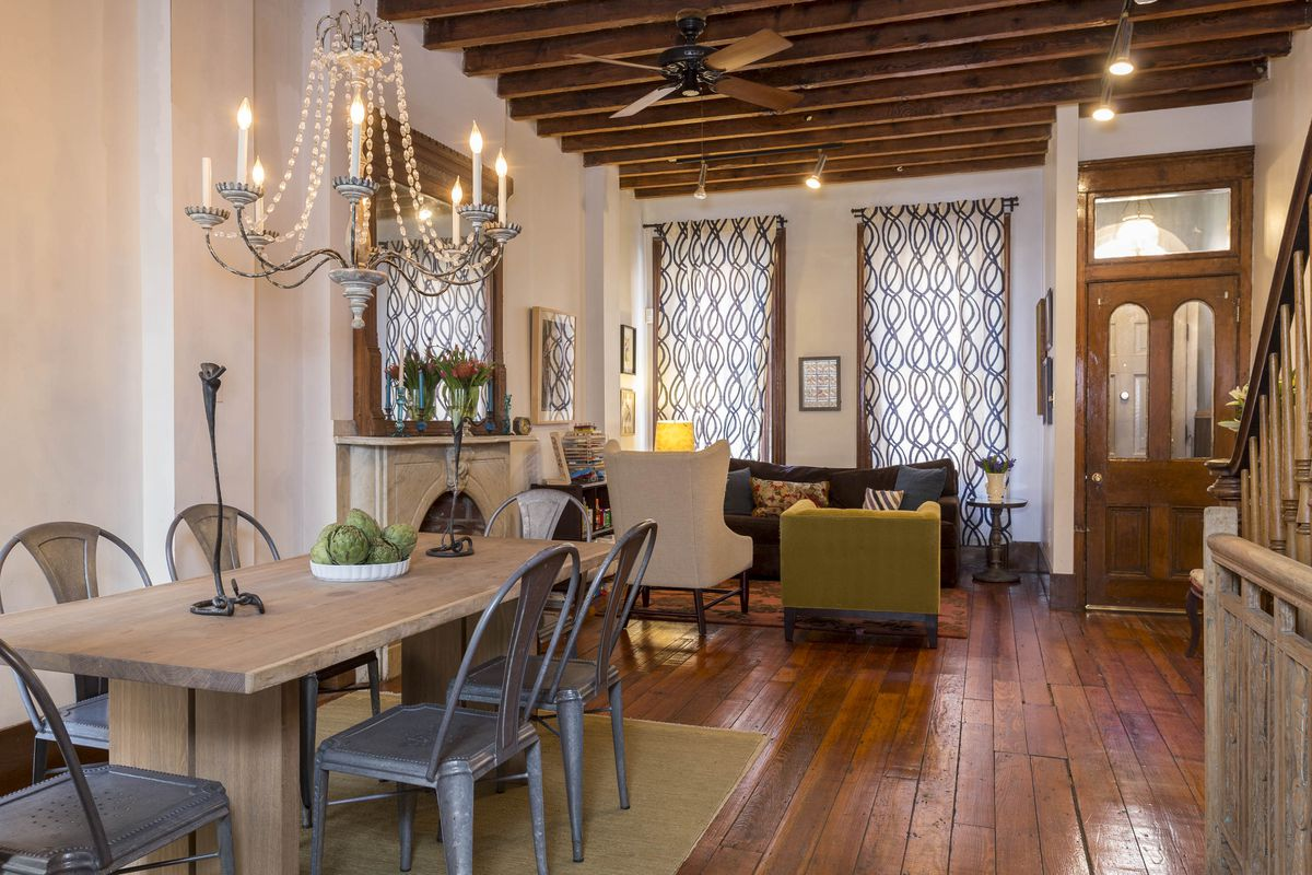 A living and dining room with a chandelier, hardwood floors, and exposed beams.