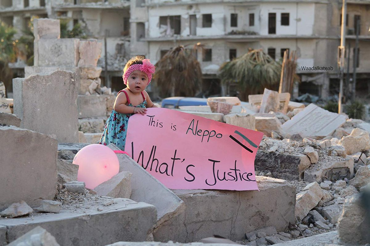 """A scene from the documentary """"For Sama"""" showing a toddler amid the wreckage of Aleppo holding a sign that reads, """"What's justice."""""""