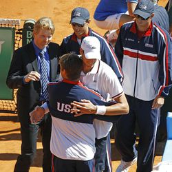 U.S. player John Isner is congratulated by teammate Ryan Harrison, as team captain Jim Courier, left, and players Bob and Mike Bryan look on, after winning his match against French player Jo-Wilfried Tsonga, in the quarterfinal of the Davis Cup between France and U.S. in Monaco Sunday April 8, 2012. The U.S. team qualifies for the semi-final. (AP Photo/Remy de la Mauviniere)