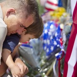 Duane Oliver of Prescott Valley hugs his son, Conner Oliver, 2, by a memorial for the fallen firefighters in front of Prescott Fire Station #7 on Monday, July 1, 2013. Nineteen firefighters have died in the Yarnell Hill Fire that has ripped through half of the town and sent residents to Prescott for safety. (AP Photo/The Arizona Republic, David Wallace)
