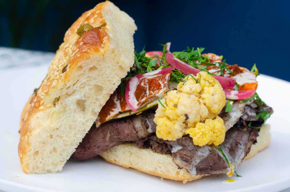 An open-faced sandwich topped with carnitas, cauliflower, cilantro, and pickled onion