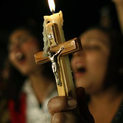 FILE - In this Sunday, Oct. 16, 2011 file photo, Egyptian Copts carry a Christian cross and a candle and chant prayers while taking part in a protest marking one week since deadly clashes between Coptic protesters and the military, in Cairo, Egypt. Egypt's estimated 8 million Coptic Christians are feeling increasingly cornered amid the rise to power of hardline Islamists after the ouster of Hosni Mubarak's longtime authoritarian regime and fear that they will bear the brunt of blame for the film that mocked the Prophet Muhammad.