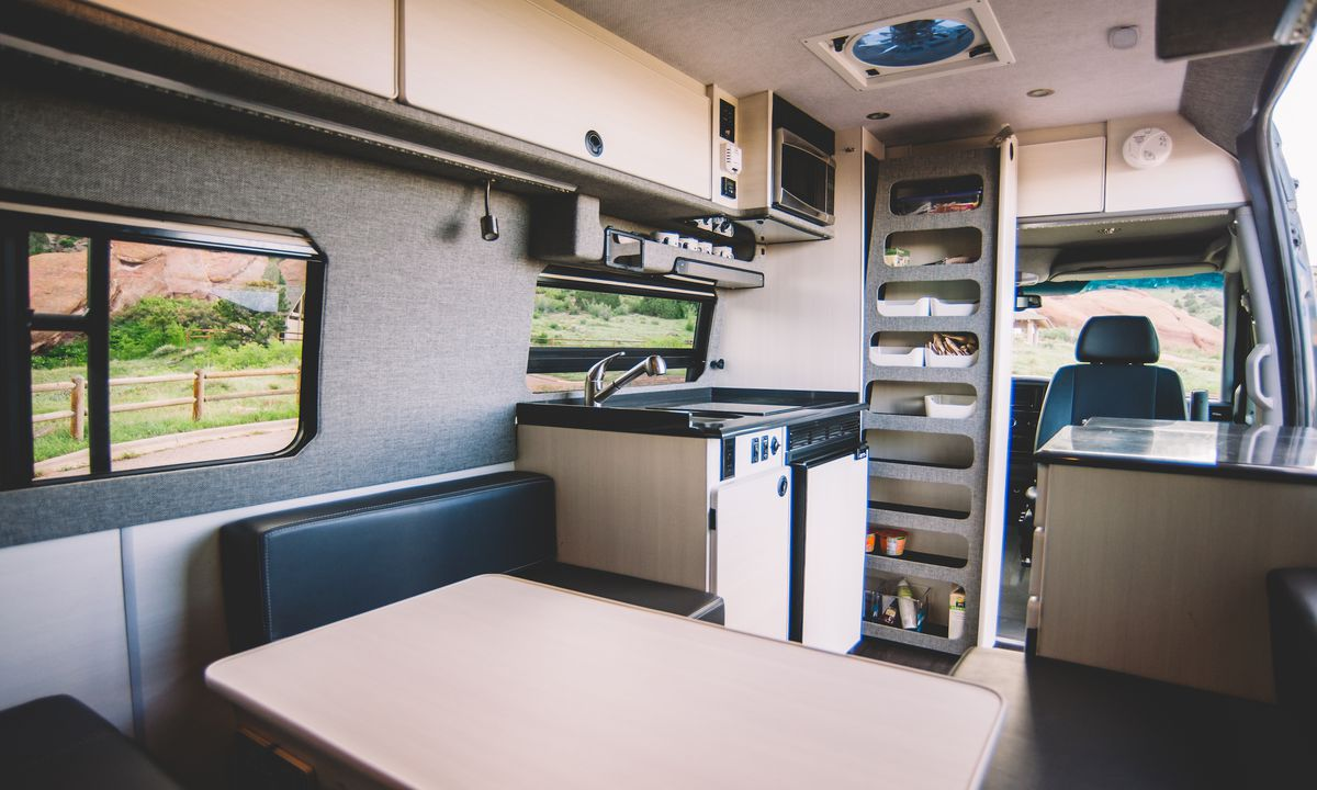 The interior of a camper van. There is a table, seats, a kitchenette, and cabinetry.