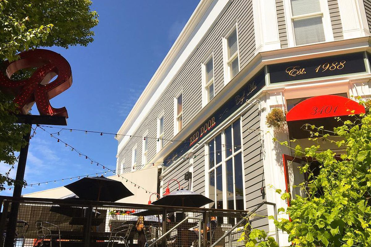 The exterior of The Red Door in Fremont on a sunny day, with a patio and a red awning out front.