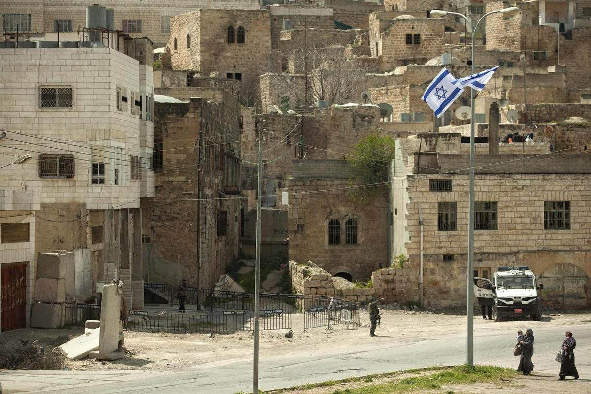 Israeli soldiers and police stand guard outside the building, on the left,  occupied by Israeli settlers in the West Bank city of Hebron, Monday, April 2, 2012.  The Israeli military on Monday ordered dozens of Jewish settlers to evacuate a three-story bu