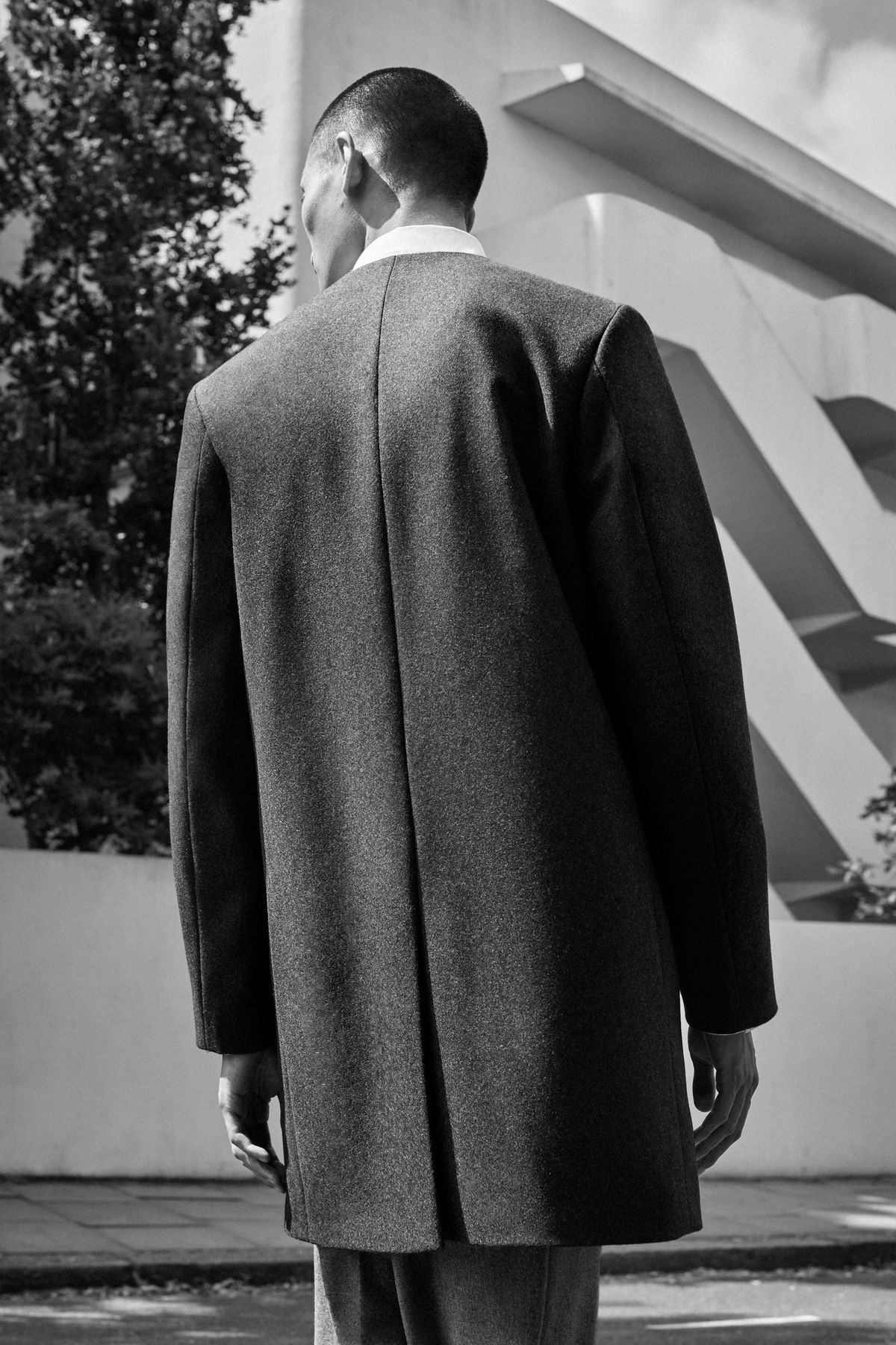 A back view of a man wearing a coat with a single slit running the entire length of the garment.