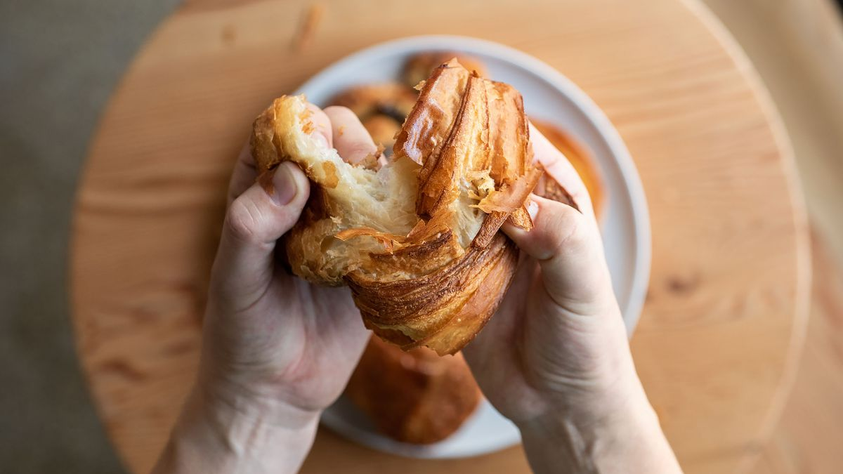 Two hands pulling apart a croissant at a bakery.