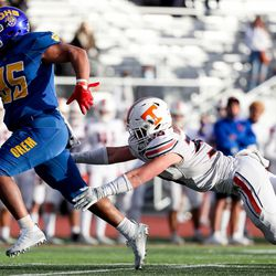 Orem's Paxton Skipps evades a tackle from Timpview's Cael Richardson as Skipps runs the ball for a touchdown, making the score tied at 6, in the 5A football state championship game at Cedar Valley High in Eagle Mountain on Friday, Nov. 20, 2020.