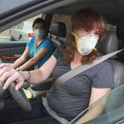 Michelle Shermer, right, and her 16-year-old daughter Nicole Shermer, who have been evacuated from wildfires and are staying in a hotel with other family members, leave a fast-food restaurant in Wenatchee, Wash., Thursday, Sept. 20, 2012. Both are preparing to try to get back to their Forest Ridge home, which is near Mission Ridge, to gather more belongings, but don't know if they will be allowed back in. Many in Wenatchee are wearing masks because the air quality is so terrible. The smoke here is as thick as fog.
