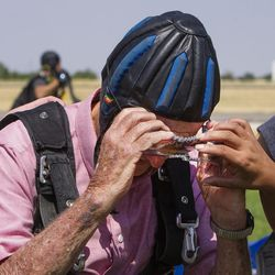 Family members and instructors reach over to help Wendell Ashcroft take off his goggles after skydiving at Skydive Ogden in Ogden on Saturday, Aug. 5, 2017.