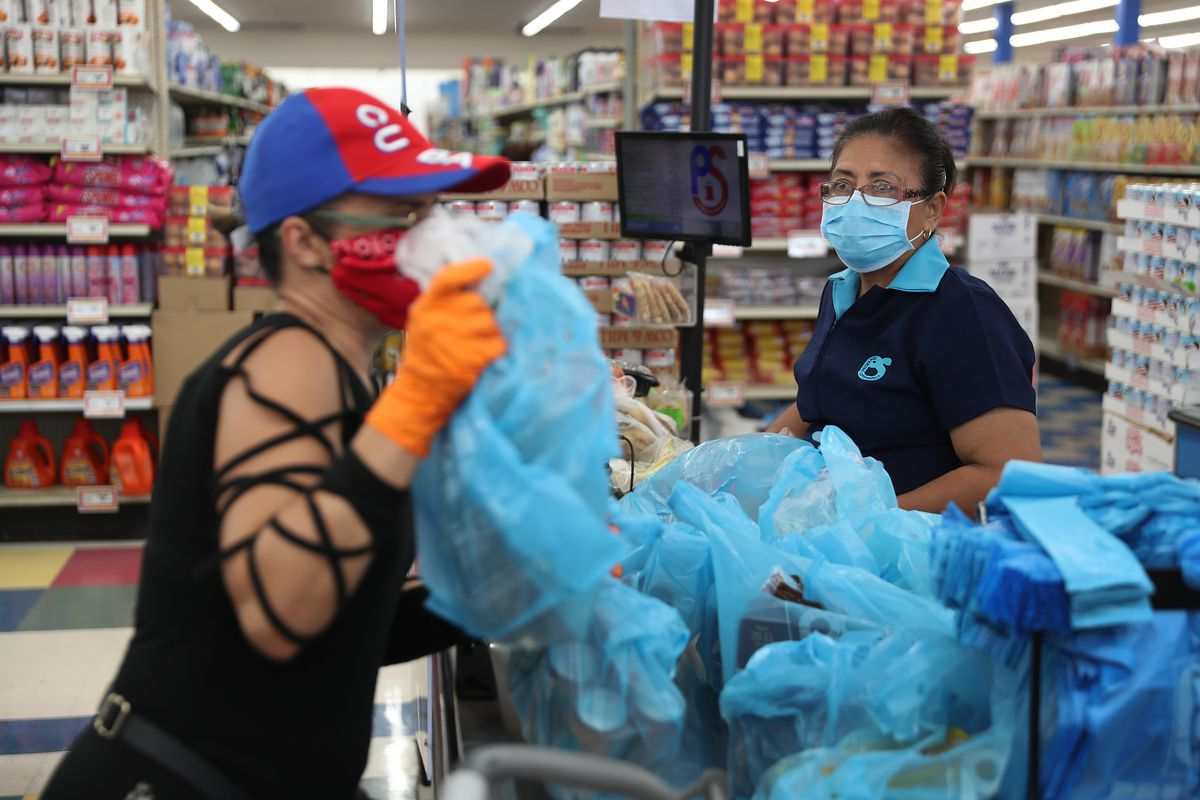Two supermarket employees wear masks and gloves as they stand behind a protective plastic screen