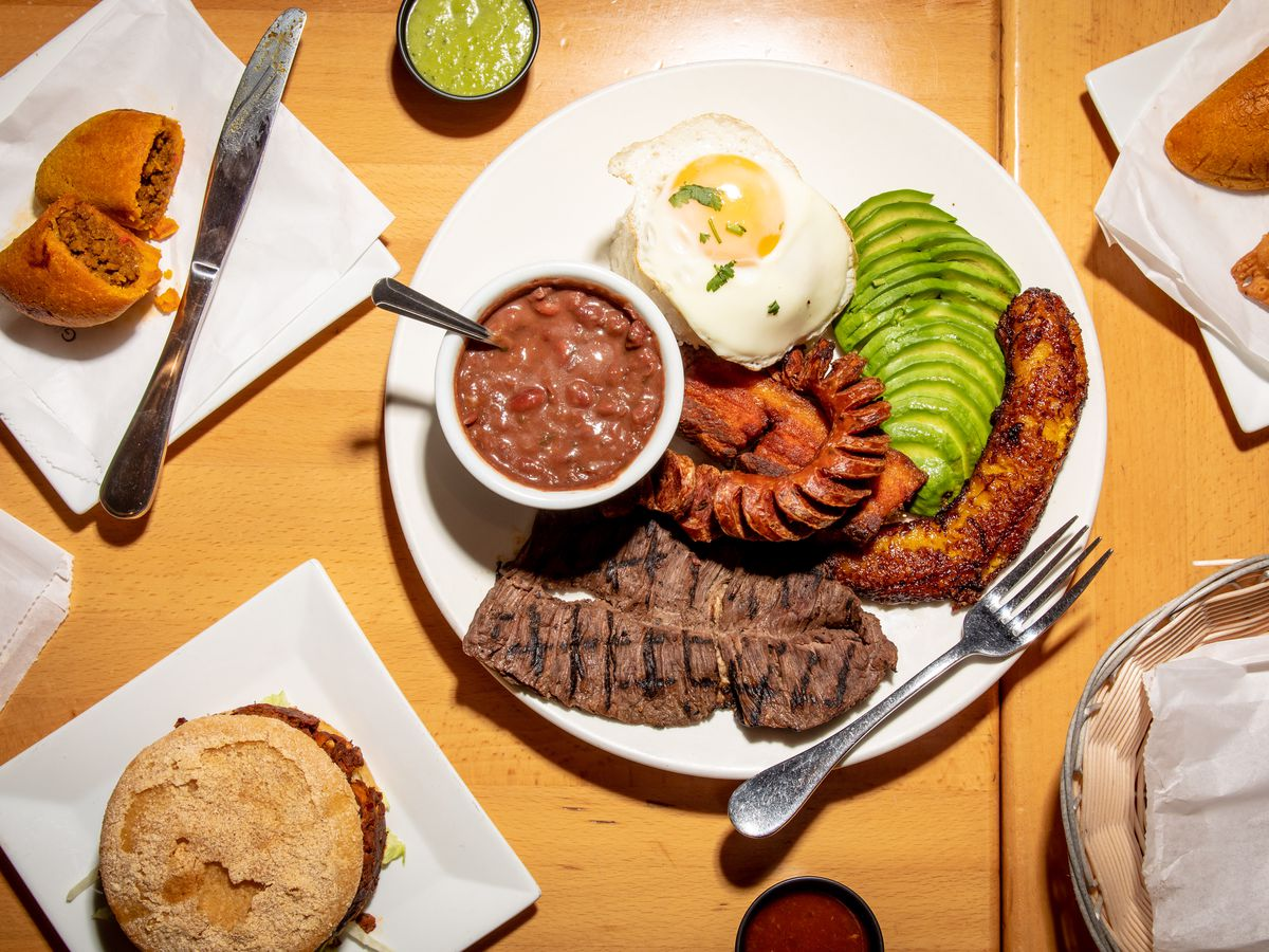 The bandeja paisa meat platter sits in the middle of the overhead photo; to the top left lies a corn and beef empanada; a spicy chicken arepa sits at the lower left-hand side of the photo