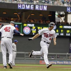 Minnesota Twins' Clete Thomas is congratulated by third base coach Steve Liddle, left, as he runs toward home plate on a two-run home run  against Texas Rangers pitcher Neftali during the fifth inning of a baseball game on Sunday, April 15, 2012, in Minneapolis. The players were all wearing No. 42 jerseys in honor of Jackie Robinson Day.