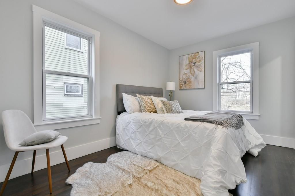 A bedroom with a bed and a chair next to it.