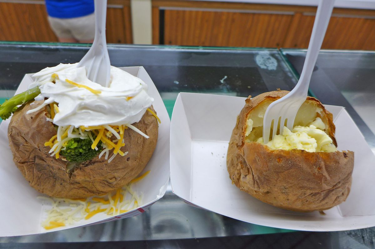 Two baked potatoes, one plain, the other with sour cream, broccoli, etc.