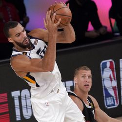 Utah Jazz's Rudy Gobert (27) grabs a rebound over Denver Nuggets' Mason Plumlee (7) during the second half an NBA first round playoff basketball game, Tuesday, Sept. 1, 2020, in Lake Buena Vista, Fla.