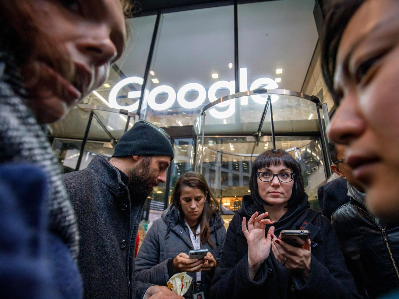 A group of Google five employees stands in front of a Google office building in London during a protest.