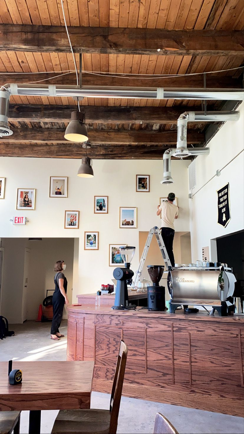 People in masks hang framed art on the walls behind a wooden coffee bar at Gathering Coffee Co.