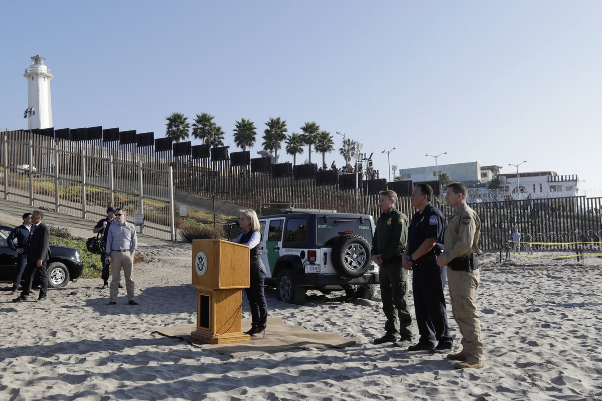 Secretary of Homeland Security Kirstjen Nielsen, center at podium, speaks in front of the border wall separating Tijuana, Mexico, behind, and San Diego, Tuesday, Nov. 20, 2018, in San Diego. Nielsen said Tuesday an appeal will be filed on the decision by