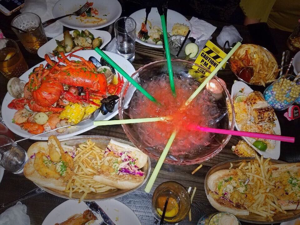 Overhead view of a table crowded with seafood dishes and a giant shareable pink cocktail with six colorful straws coming up out of it.