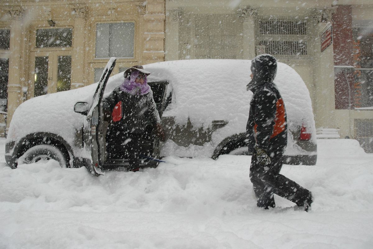 Kriz Kizak (L) prepares to clean off her sport utility vehicle in blizzard conditions February 12, 2006 in the Soho neighborhood of New York City.
