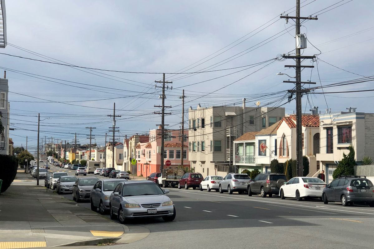 A long stretch of street with parked cars, colorful houses, and telephone pole wires.
