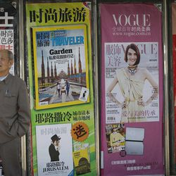 An elderly man stands in front of magazine posters in downtown Beijing, China, Friday, April 13, 2012.  China's economic growth fell to its lowest level in nearly three years in the first quarter but analysts said the economy should rebound in coming months.