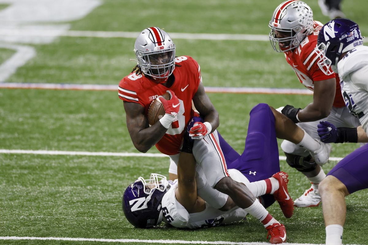 Earnest Brown IV of the Northwestern Wildcats tackles Trey Sermon of the Ohio State Buckeyes in the first quarter of the Big Ten Championship at Lucas Oil Stadium on December 19, 2020 in Indianapolis, Indiana.