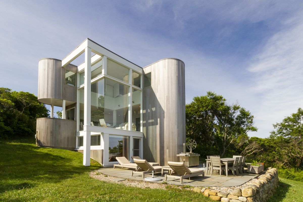 A contemporary house with two elongated towers on either side of a white and glass boxy living room that's open to views.