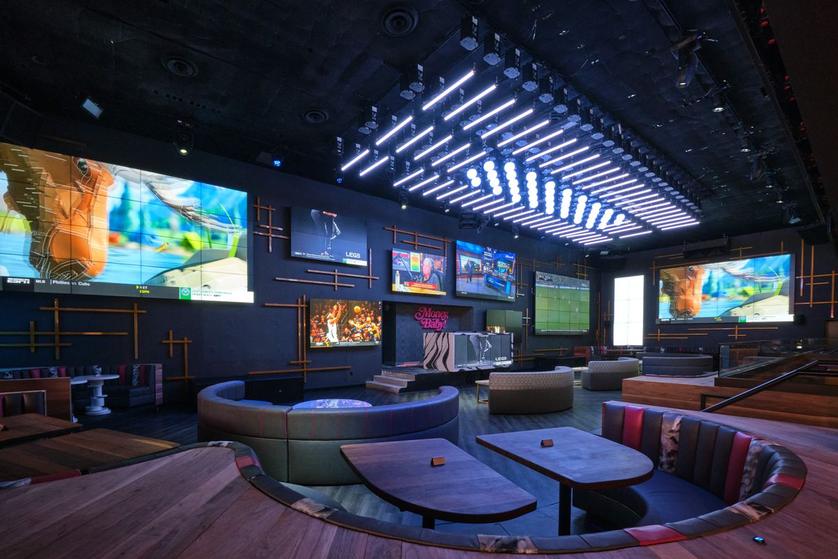 A dance floor with booths and TV screens on the wall