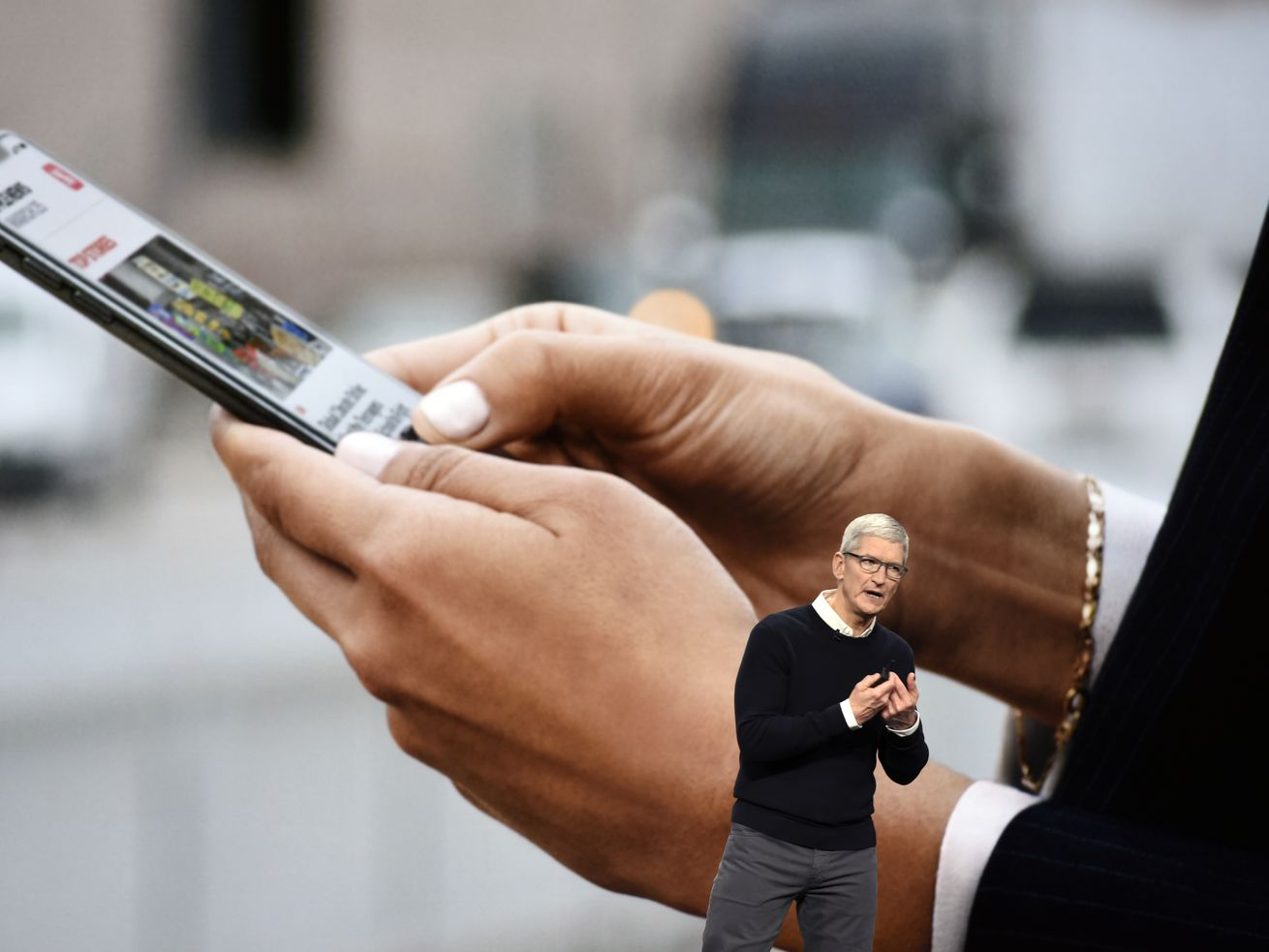 Apple CEO Tim Cook onstage in front of a wall-sized screen showing two hands holding an iPhone.