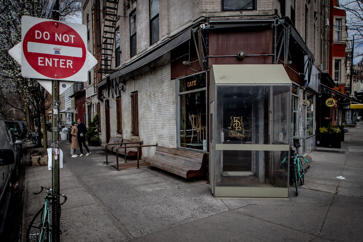 A couple kisses next to a closed Five Leaves restaurant in Brooklyn