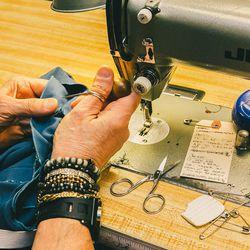 Men's Wardrobe Stitcher Jose Gutierrez sews toy soldier pants.