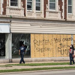 People pass by a boarded-up shop in Kenosha Tuesday afternoon, Aug. 25, 2020, after a night of unrest following the shooting of Jacob Blake by a police officer in Kenosha Sunday.