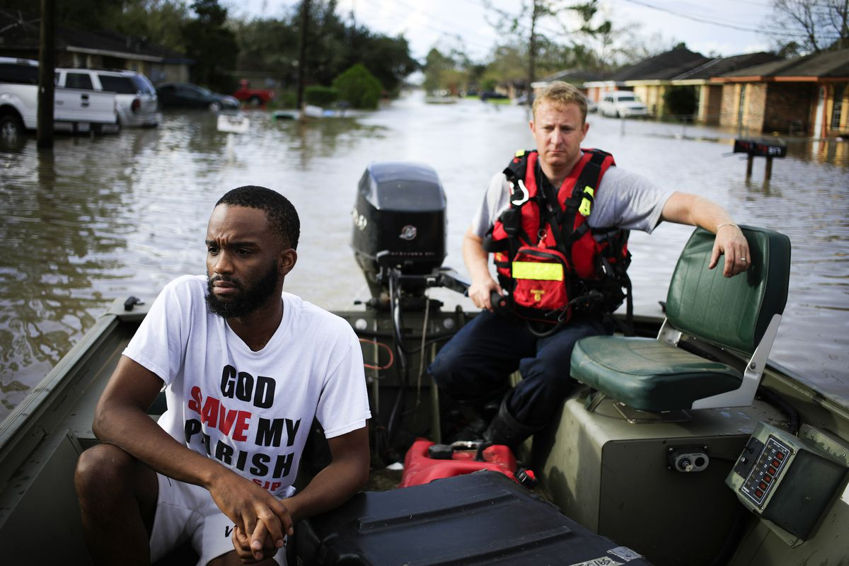 Two people in a rescue boat on a flooded street.