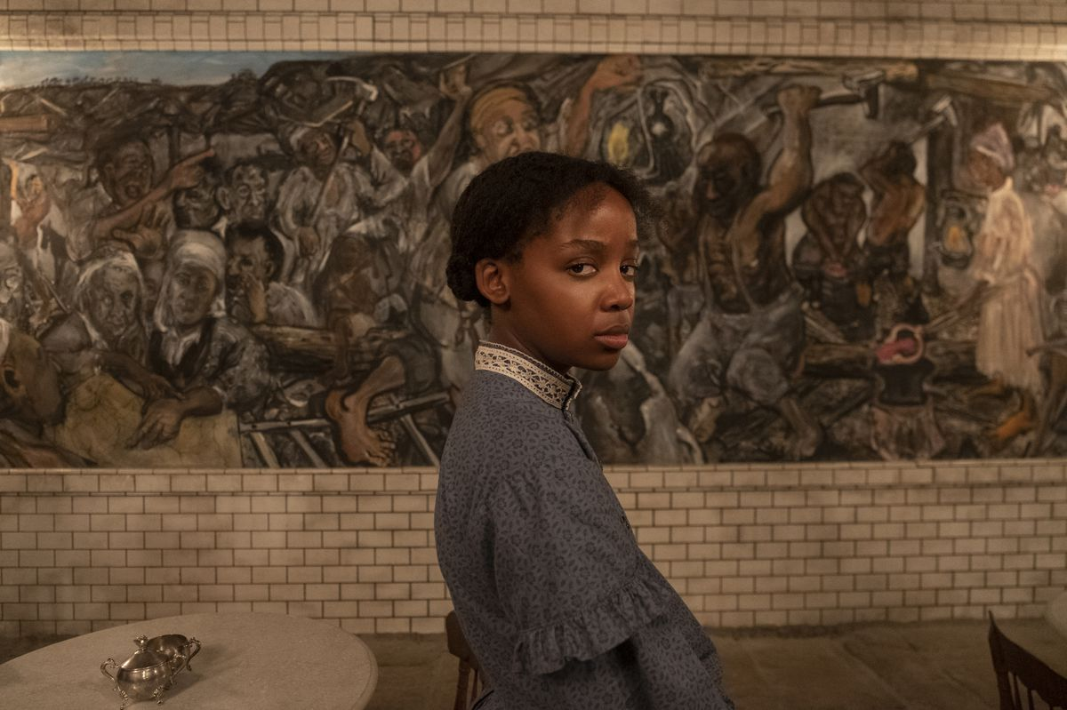 Cora (Thuso Mbedu) stands in front of an elaborate mural in an underground railroad station in Barry Jenkins' The Underground Railroad