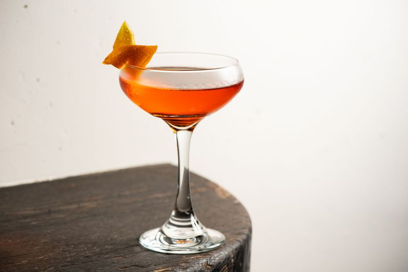 A bright orange cocktail, served up, at the edge of a table.