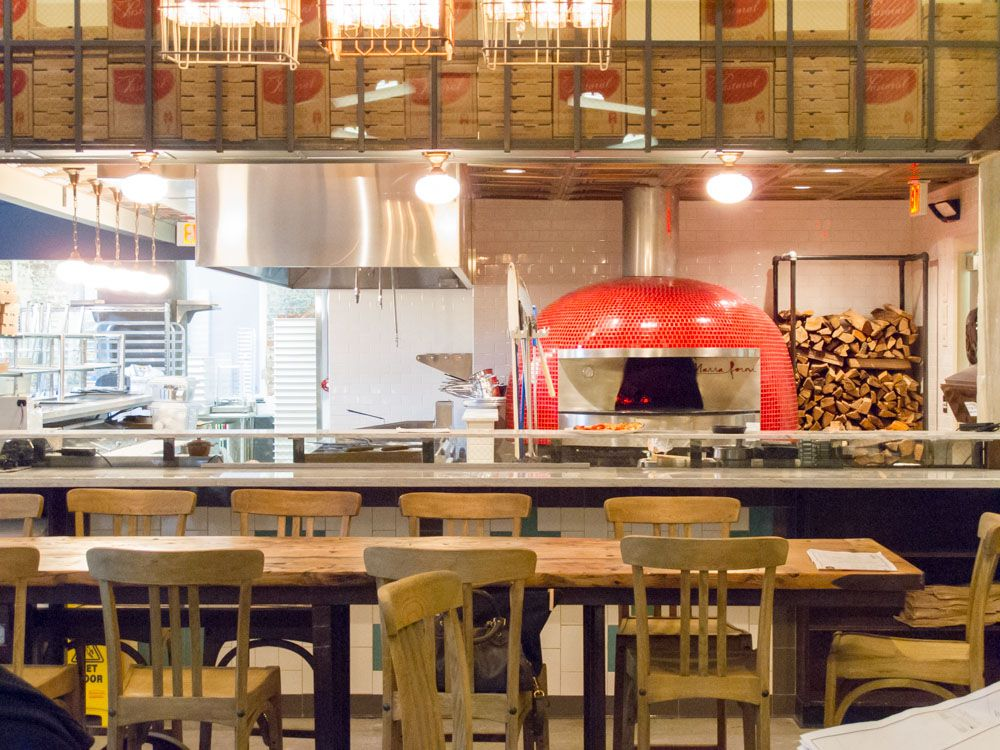 Photo of a restaurant interior, including a shiny red pizza oven with wood stacked behind it