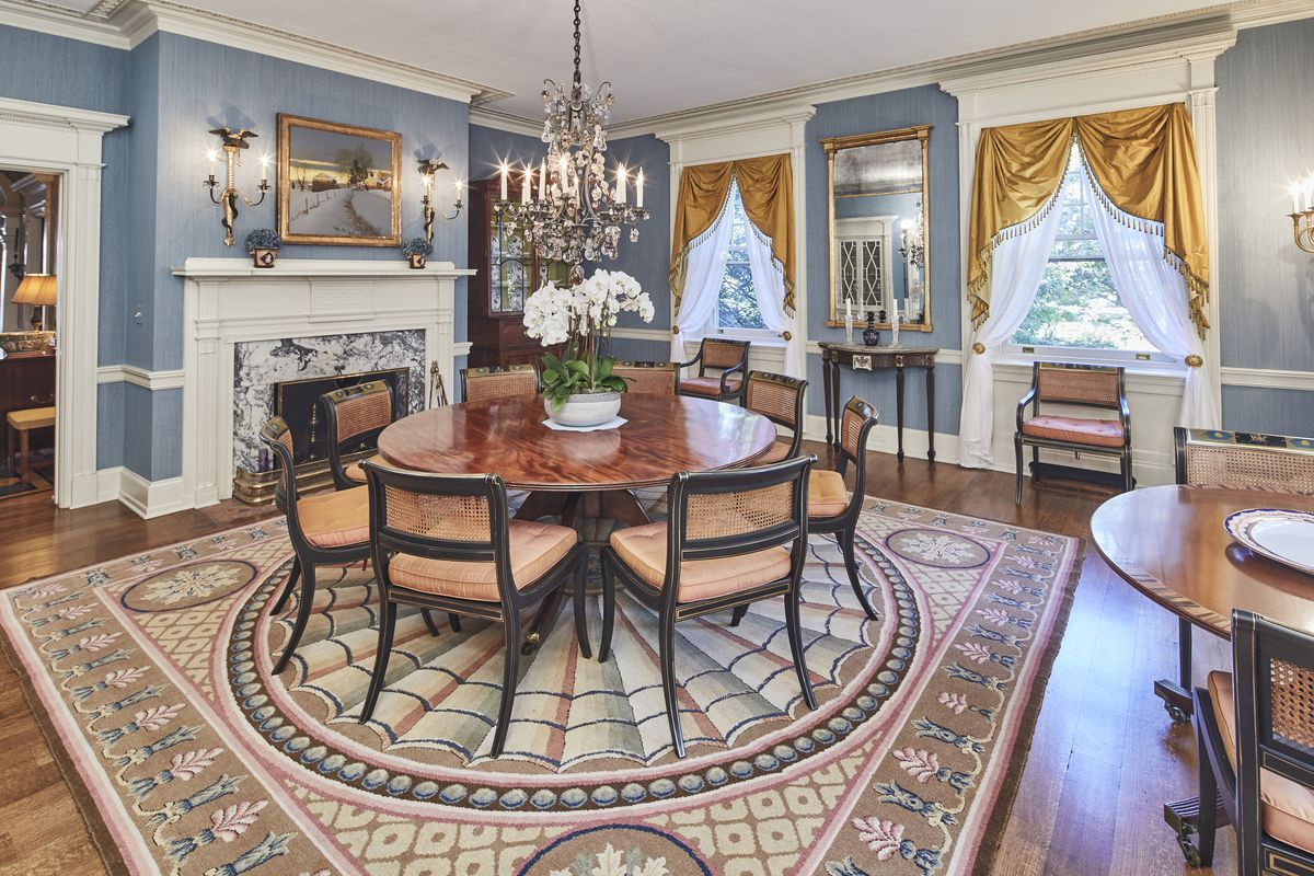 A formal dining room has blue wallpaper, gold curtains, a marble fireplace, and a large round dining table.