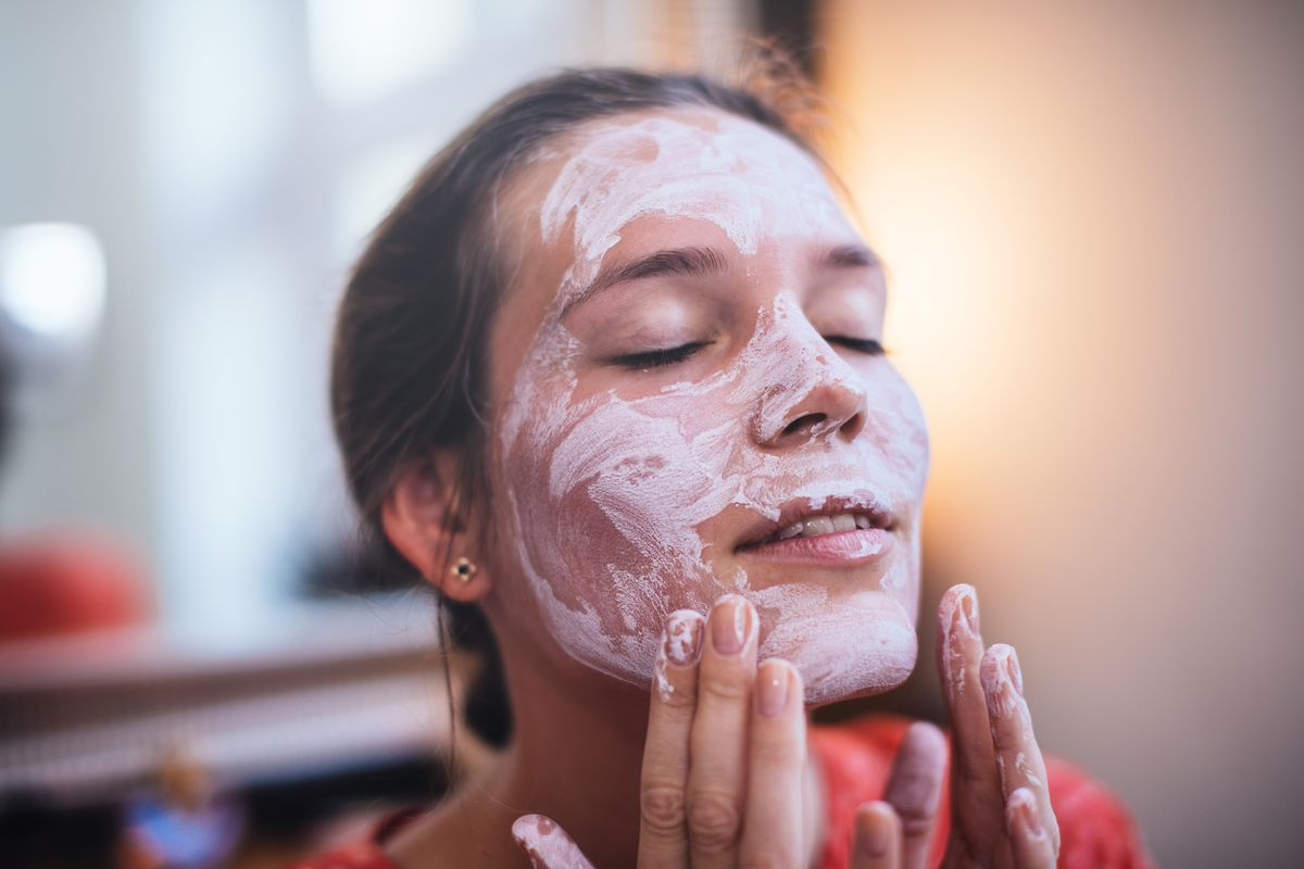 A woman putting on a face mask