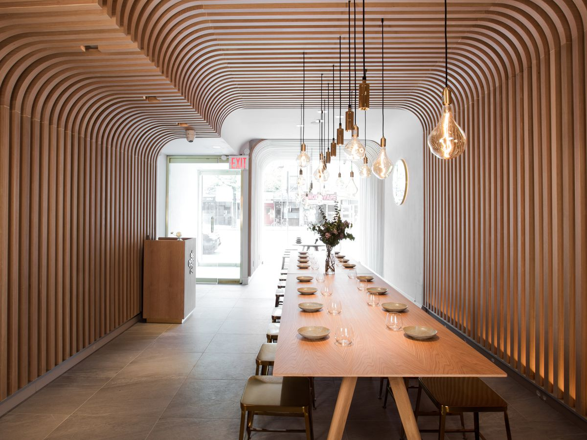 An artistic dining room with blonde wood slats from floor to ceiling and hanging exposed bulb lights
