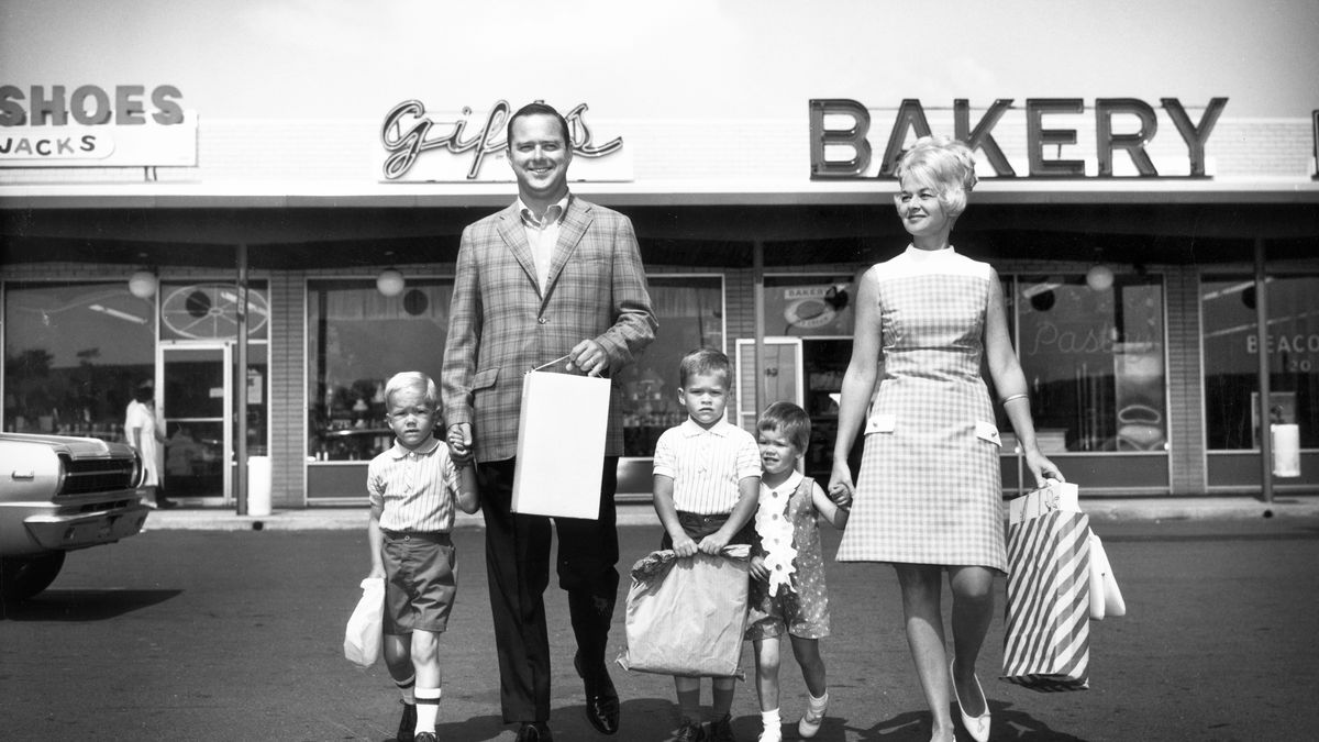 A white Americana-looking family walks out of a strip mall with shopping bags circa 1965.