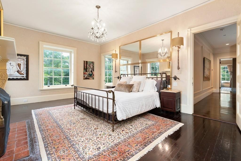 A spacious bedroom with a bed and a mirror above the bed.